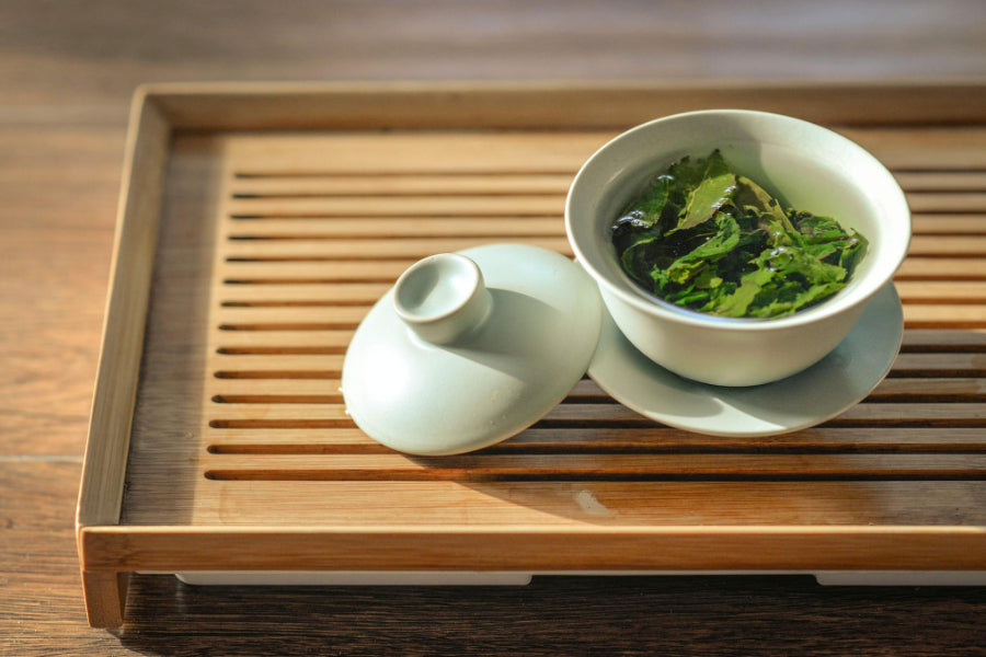 green tea leaves in white cup on wooden tray