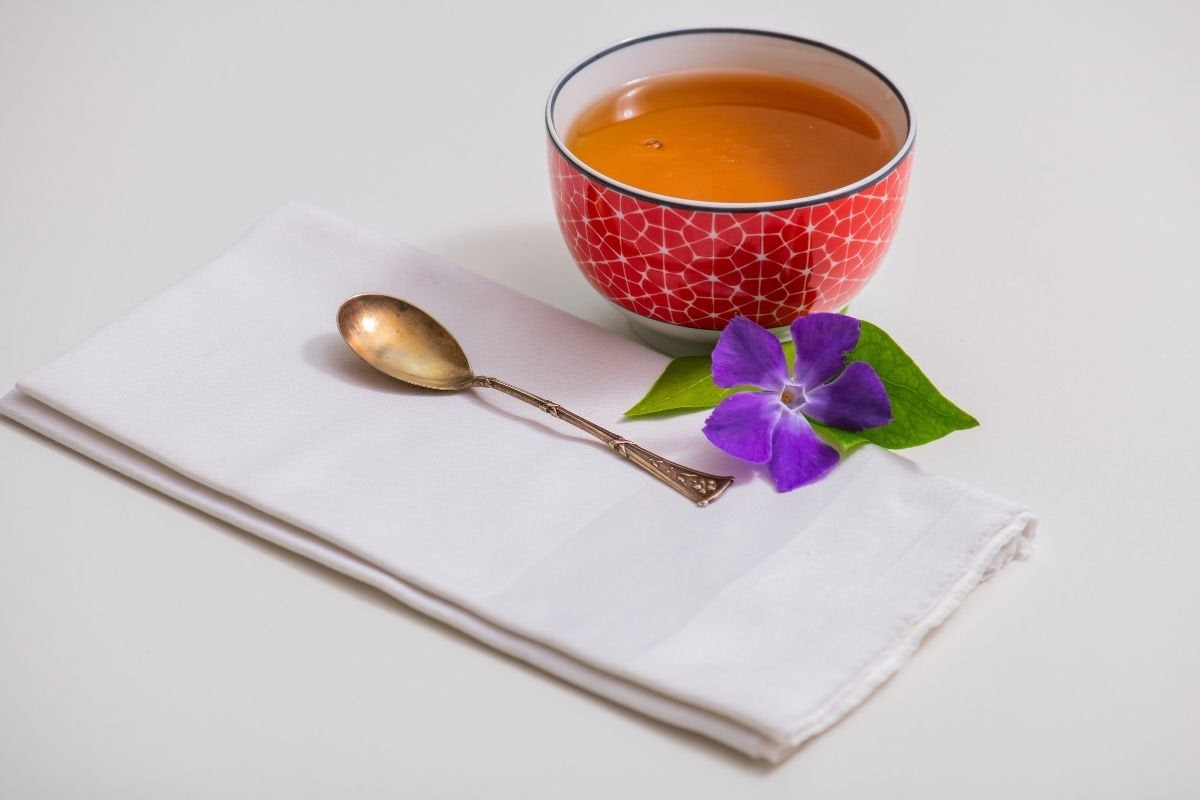 tea with white napkin, spoon and flower