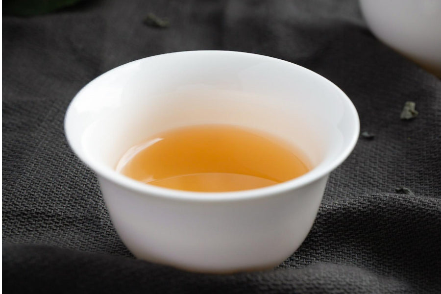 White tea in white cup against black background