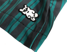 Load image into Gallery viewer, This is a photo of the SleeperBear black and white logo on the green and black stripped Hamfast athleisure shorts