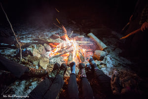 a big campfire with people warming their feet over the embers