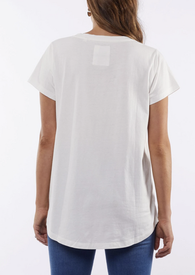 Back image of a woman in a short sleeved white t-shirt. There is a small cuff on the sleeves. The bottom of the back of the tee is a curved hem.