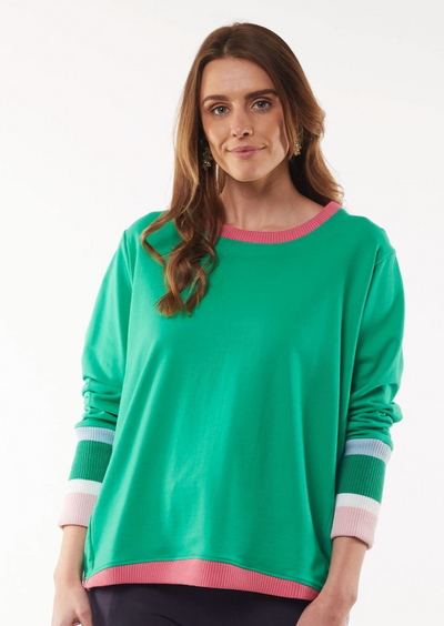 Image of woman in a long sleeved green crew. There is a hot pink trim on the crew neck and bottom of the jumper. The long sleeves also have stripes at the bottom that start from bottom third of the arm. The stripes from top to bottom are as follows: thin blue, thick green, thin white and thick baby pink stripe. Bottom of sleeves are elasticised.