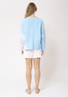 Back view of blonde women wearing a light blue long sleeved jumper, bottom left of the jumper and left sleeve is a tie-die design. The tie-die colouring is white, lilac and light pink. This jumper is paired white white shorts and nude sandals.