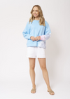 Front view of blonde women wearing a light blue long sleeved jumper, bottom left of the jumper and left sleeve is a tie-die design. The tie-die colouring is white, lilac and light pink. This jumper is paired white white shorts and nude sandals.