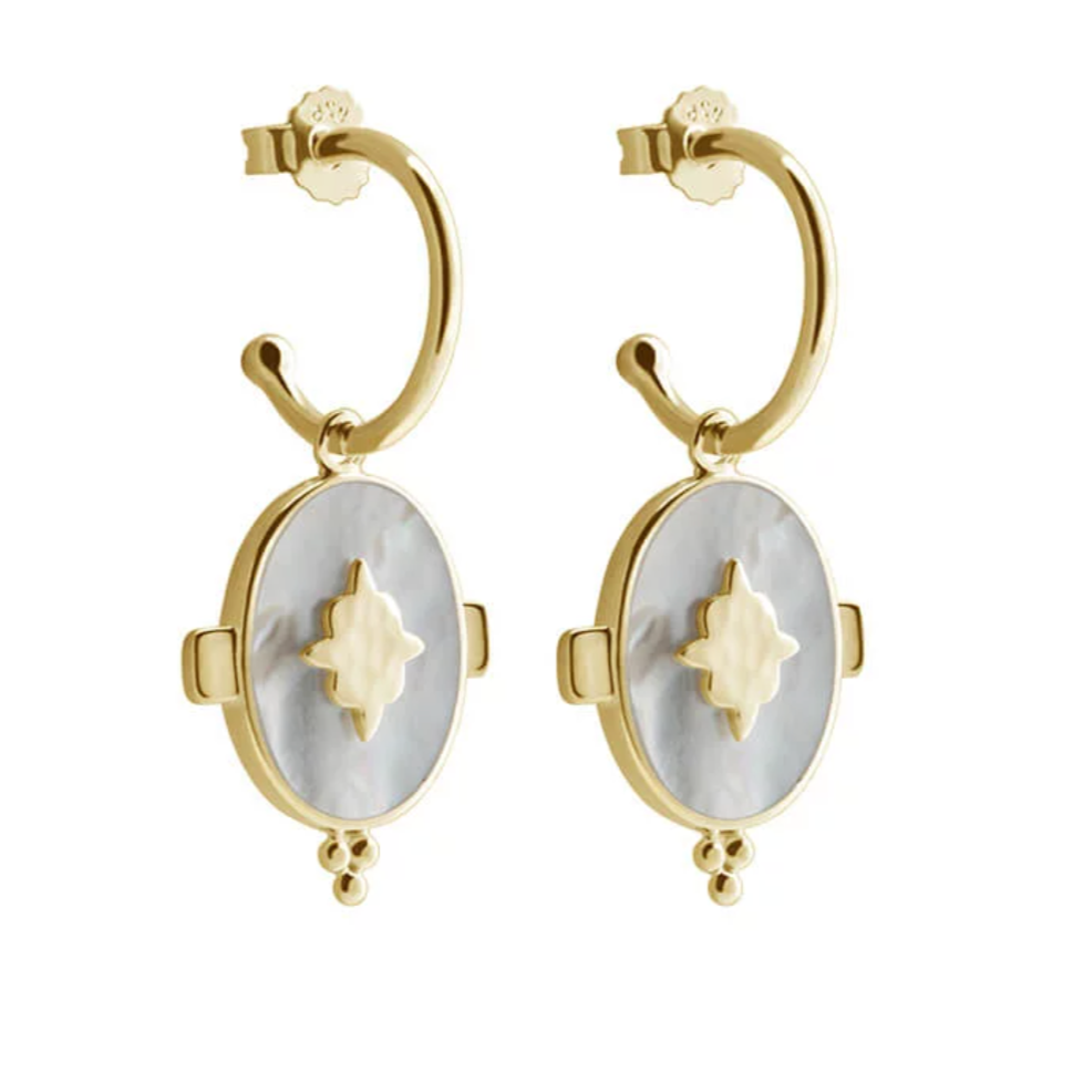 Gold plated oval earrings, hoop above attached to oval mother of pearl shape with a gold flower type pattern in the middle.