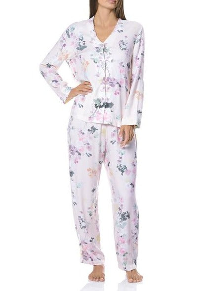 Brunette female wearing silk looking light pink pyjamas with floral patterns in purple, pink and greens.