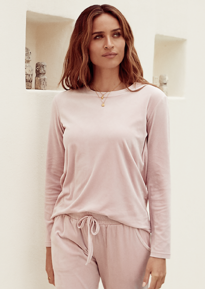 Brunette female in a matching long sleeved pink top with  pants with a draw string top.