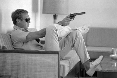 Steve McQueen Aims a Pistol in his Living Room