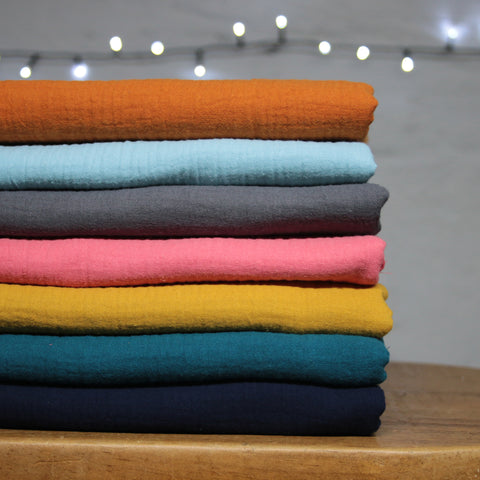 a pile of seven different coloured double gauze fabrics sitting on a wooden bench with white Christmas lights twinkling in the background.