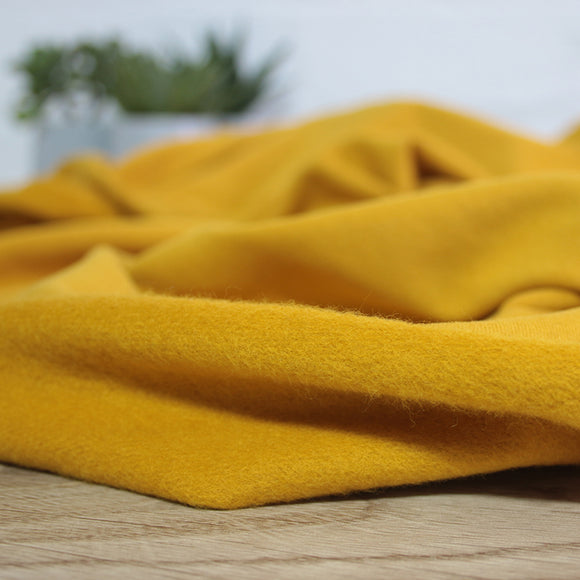 Close up of mustard yellow brushed back french terry fabric