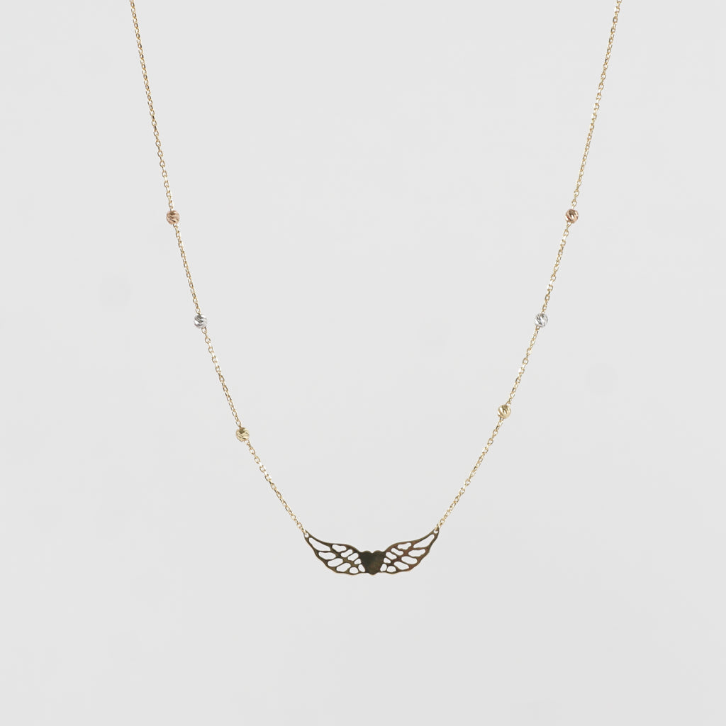 Pure 18k Gold winged heart which is permanently attached to an 18k gold chain. The chain has six sparkling round globes positioned equally on either side of the winged heart. Effortlessly stylish.