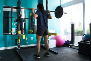 Girl using Squat Rack - Manic Fitness
