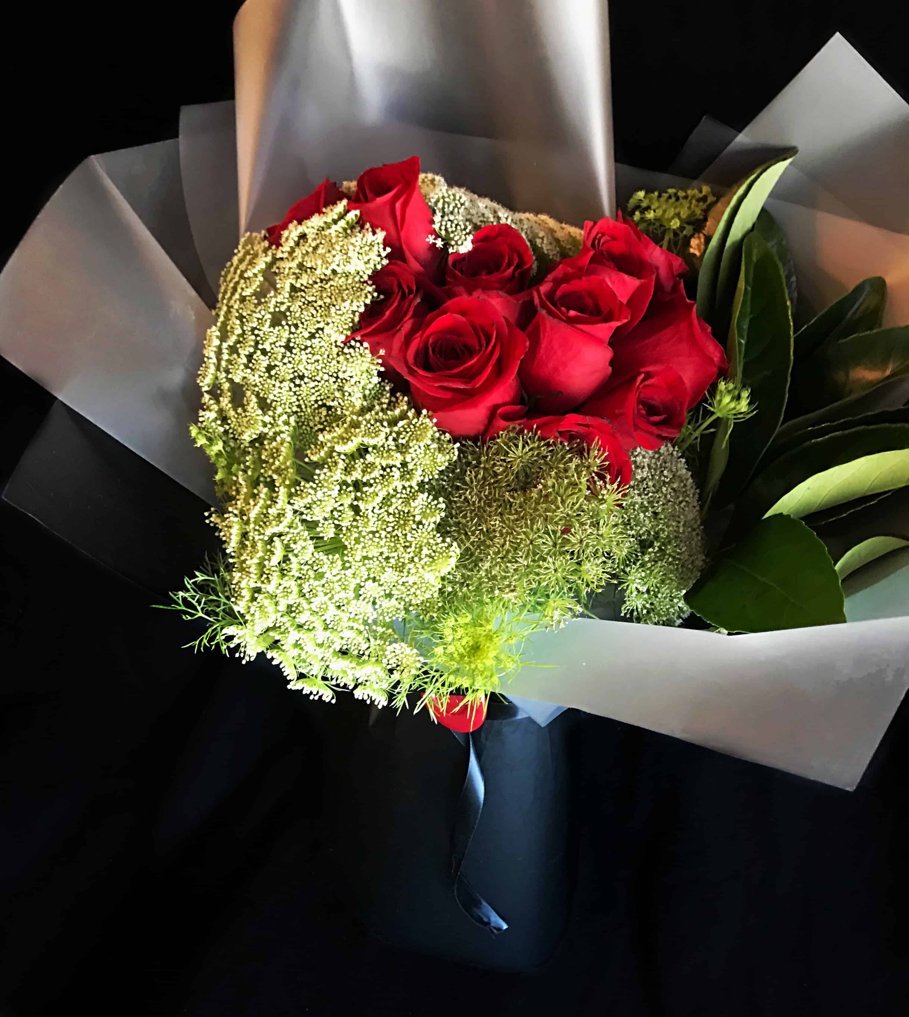 One dozen red roses with seasonal foliage wrapped with transparent and black thick plastified paper