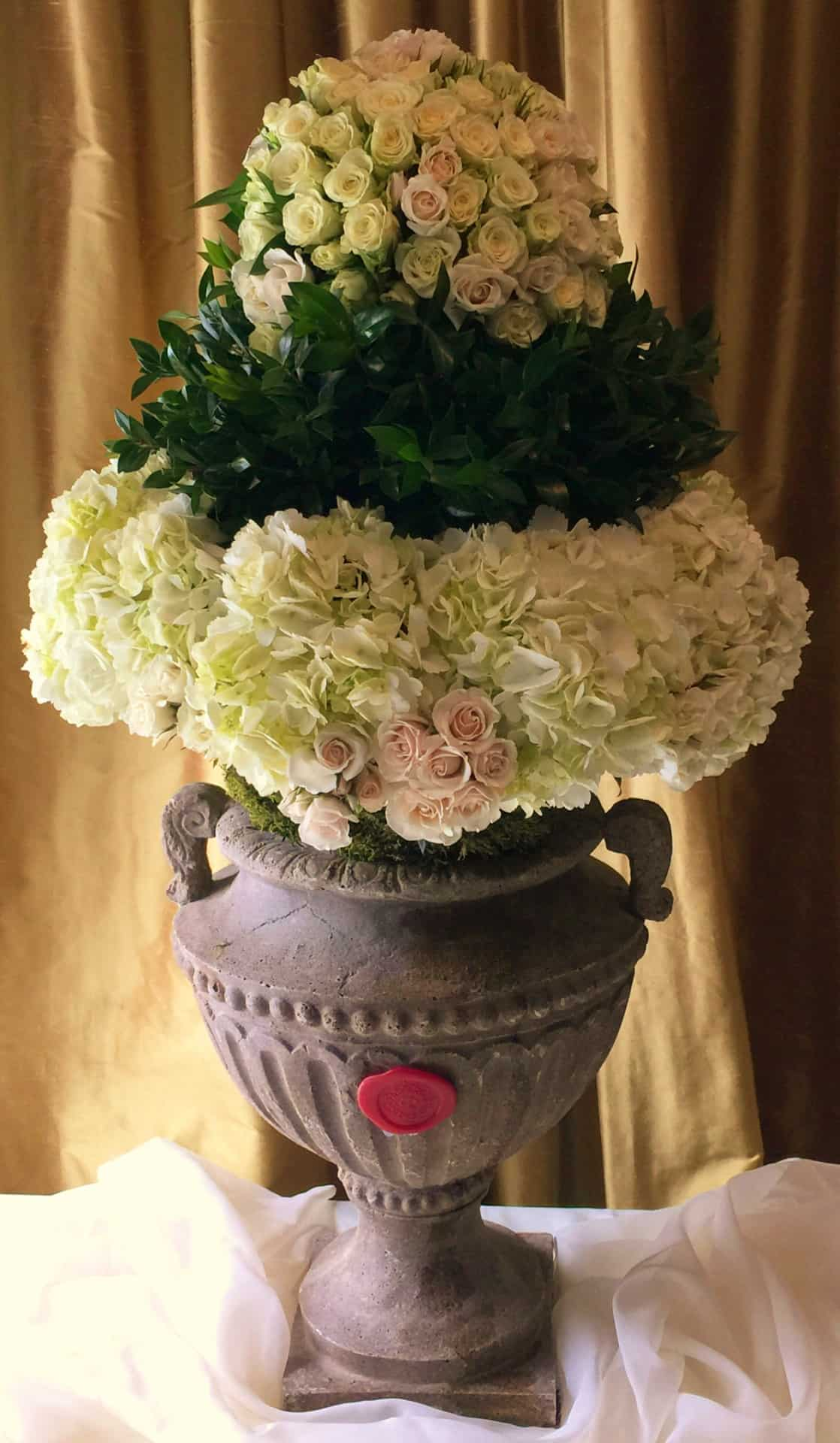 Sphere of blush spray roses, hydrangea and foliage in a gray stone urn