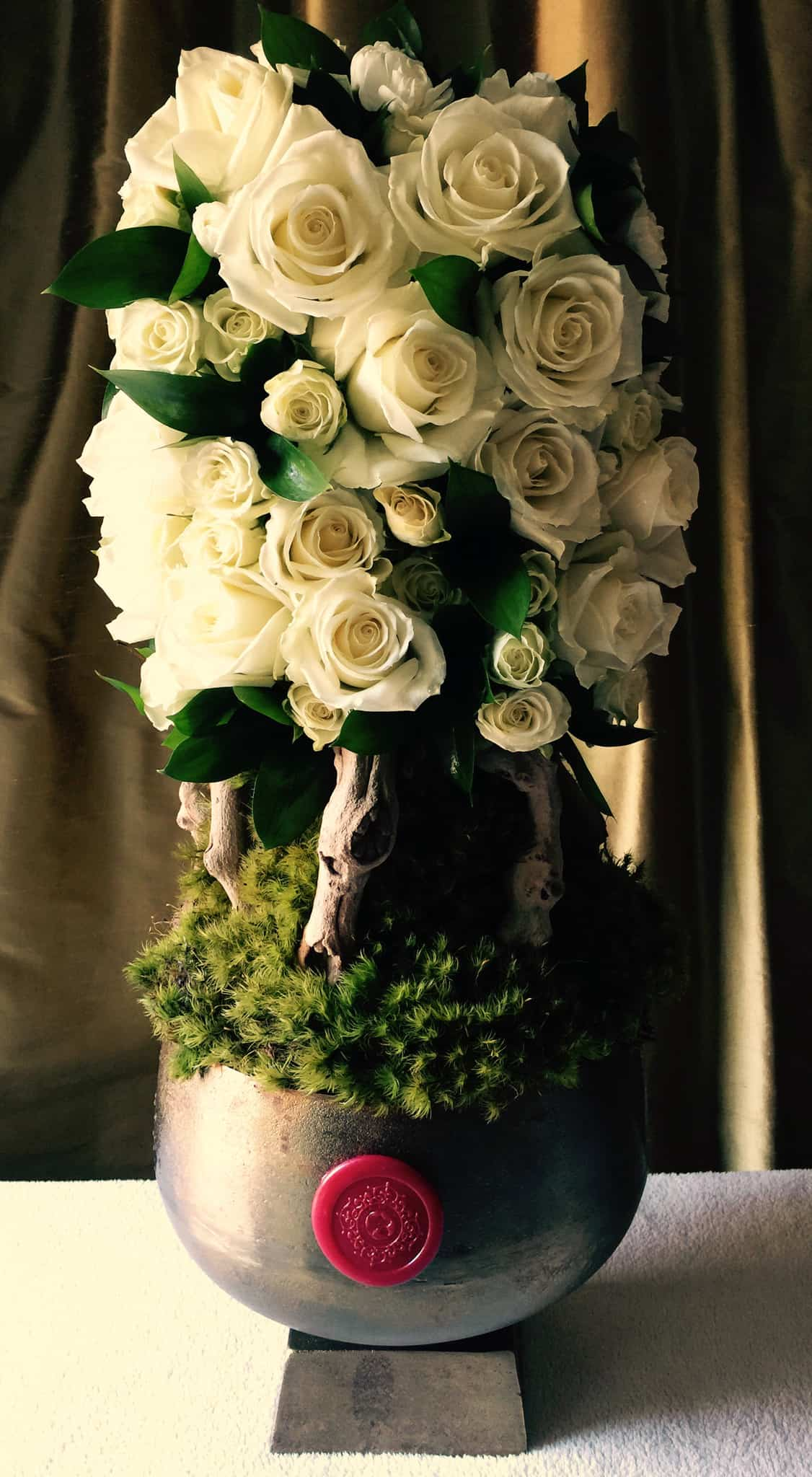 Elegant mix of white roses, white spray roses, exotic wood and foliage replicating a topiary