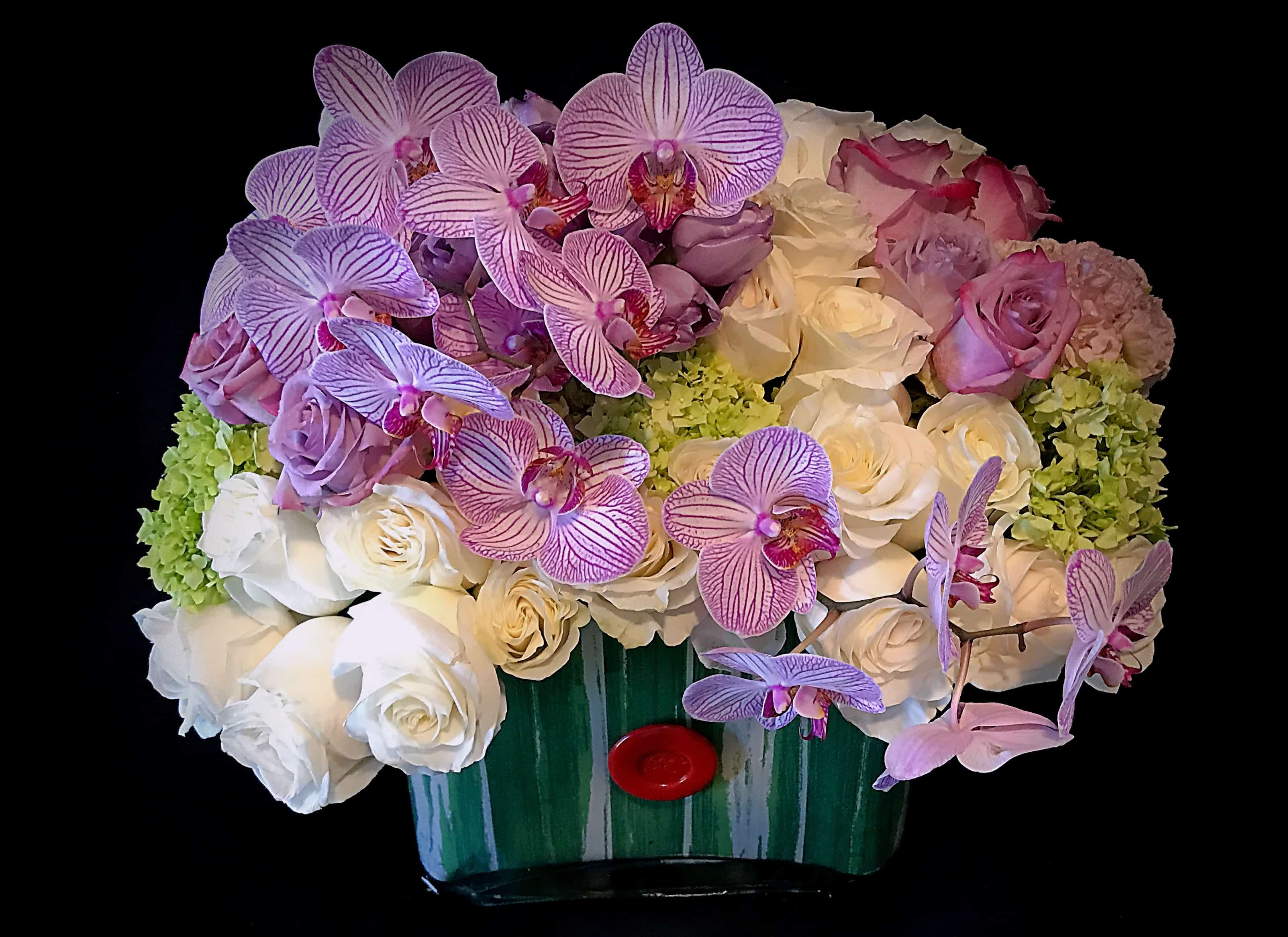 Arrangement of phalaenopsis orchids, green hydrangea, and lavender roses in a rectangular glass vase