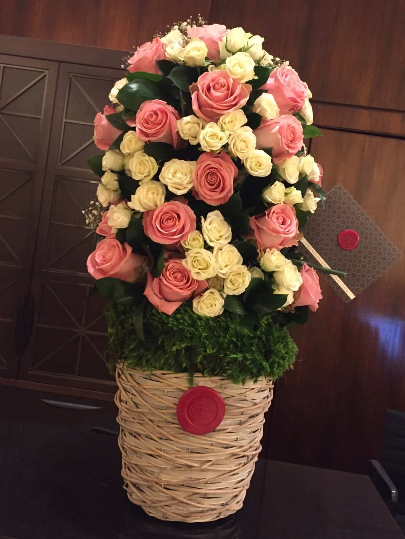 Tower of white and pink premium and spray roses with foliage over branch container with a moss