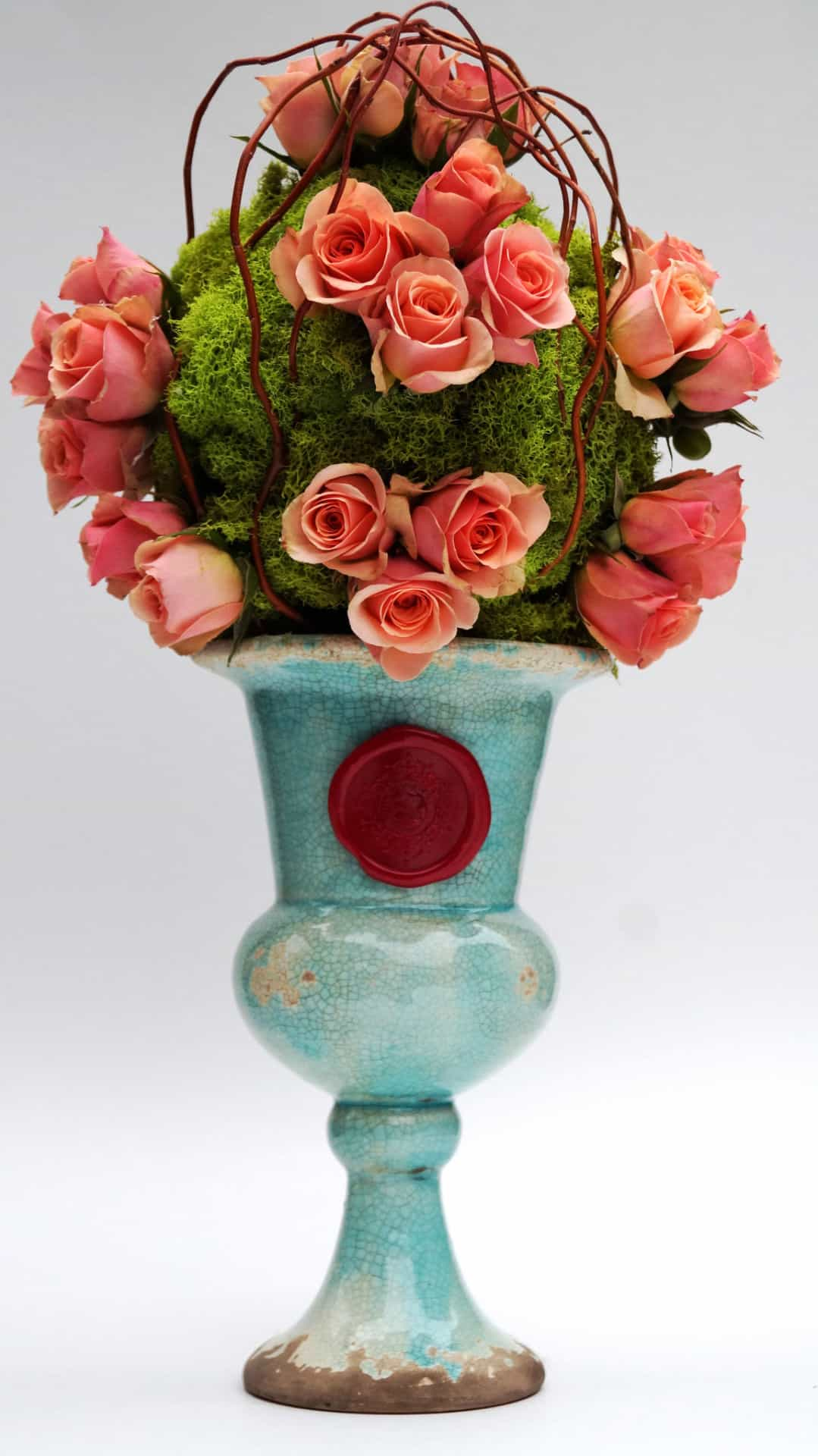 Peach rose topiary in a teal distressed urn with lime moss and curly