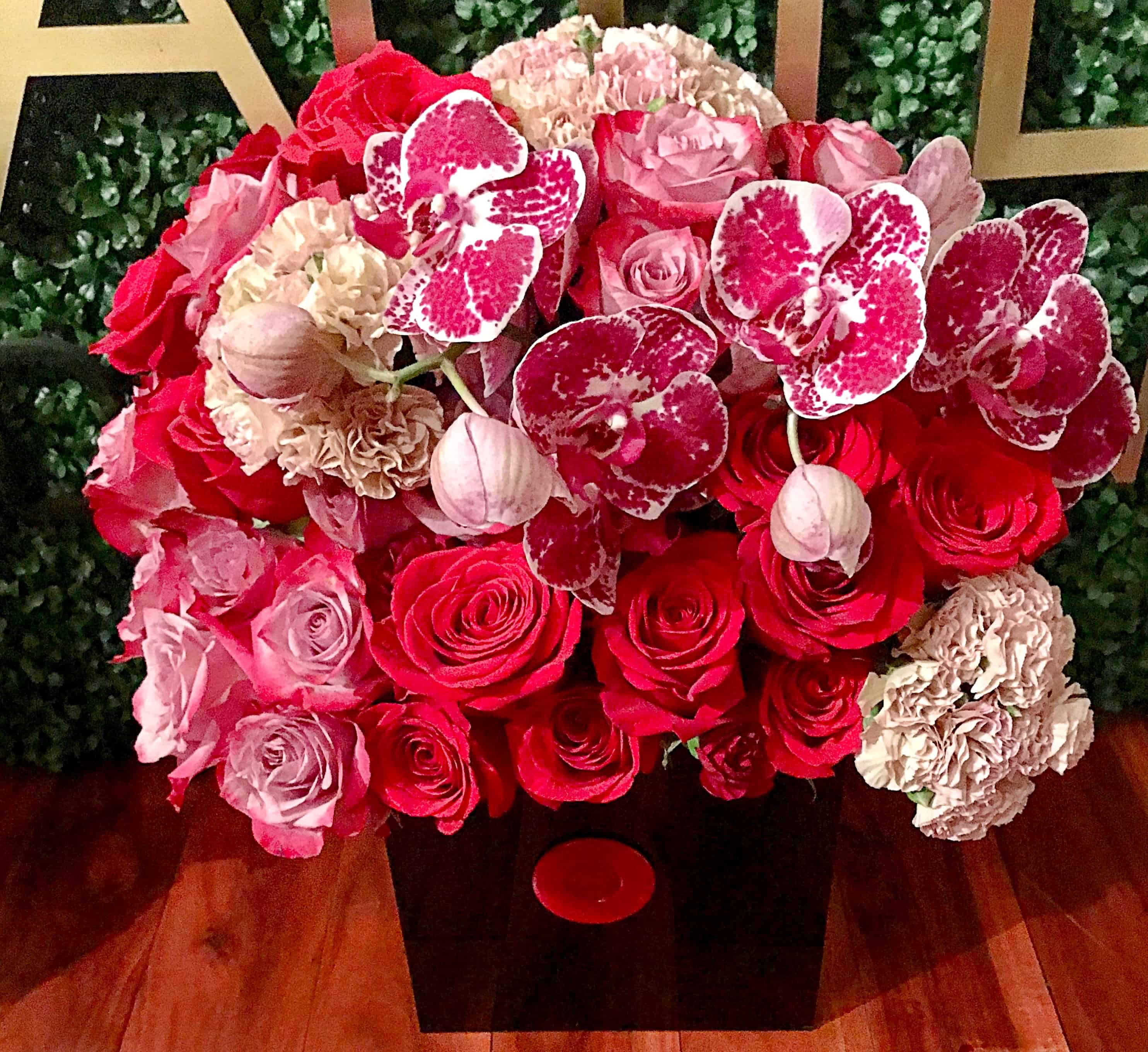 Red, and pink tones of premium roses and Phalaenopsis orchids with two spheres of seasonal flowers in our black acrylic box