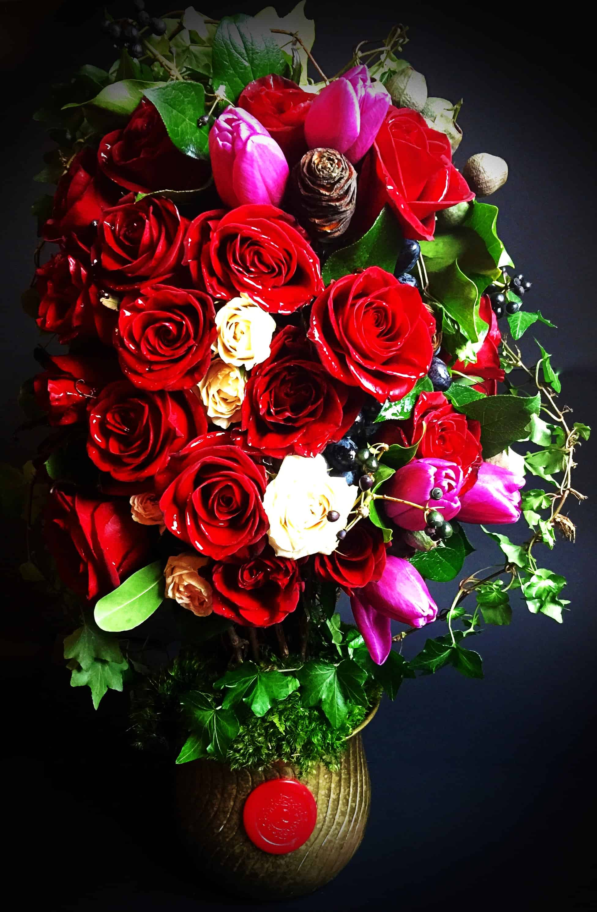 Two dozen red roses, tulips, moss, foliage and curly branches forming a topiary base