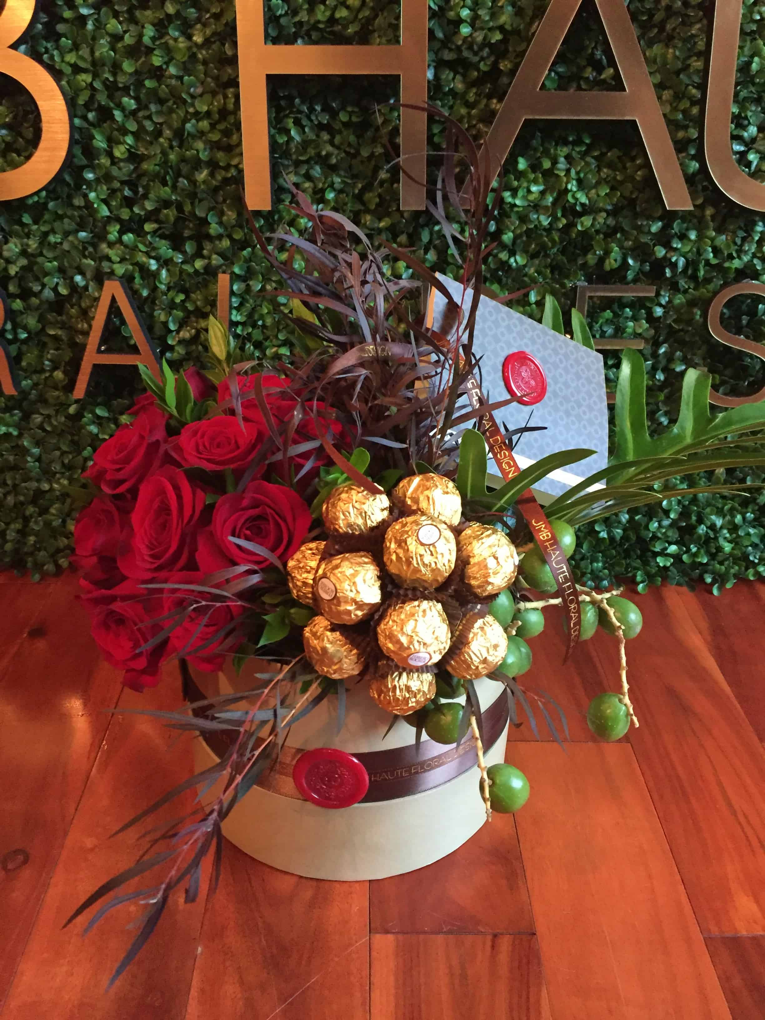 A Sphere of red roses and a sphere of chocolates surrounded by seasonal foliage in a round box