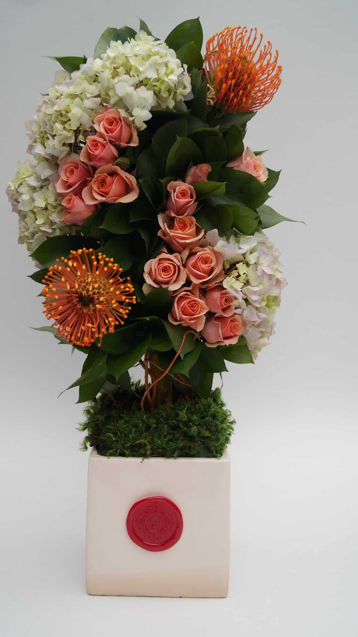 Combination of hydrangea, coral roses, protea and curly branches
