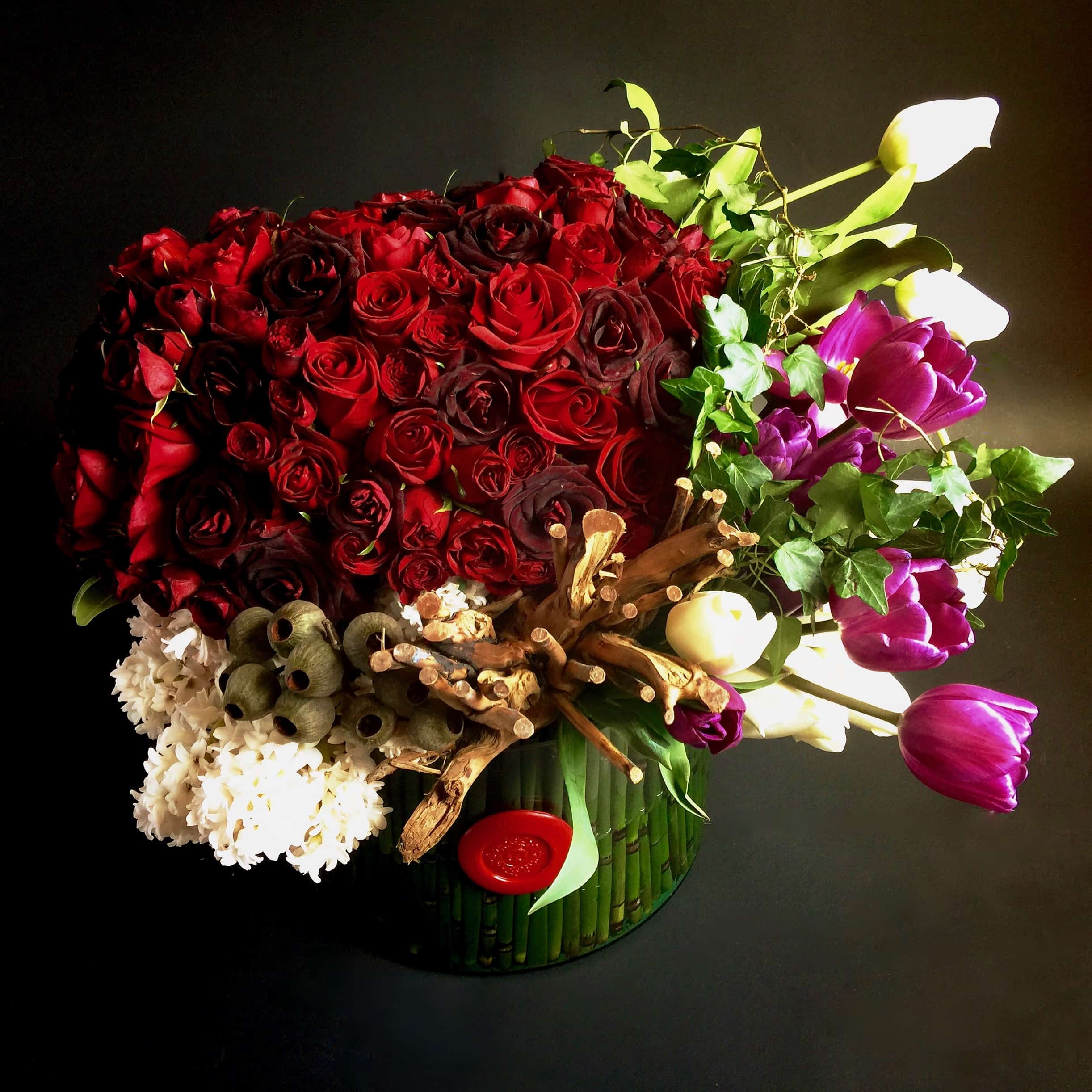 Handpicked premium red roses, tulips, grapevine and ivy over a lined glass cylinder