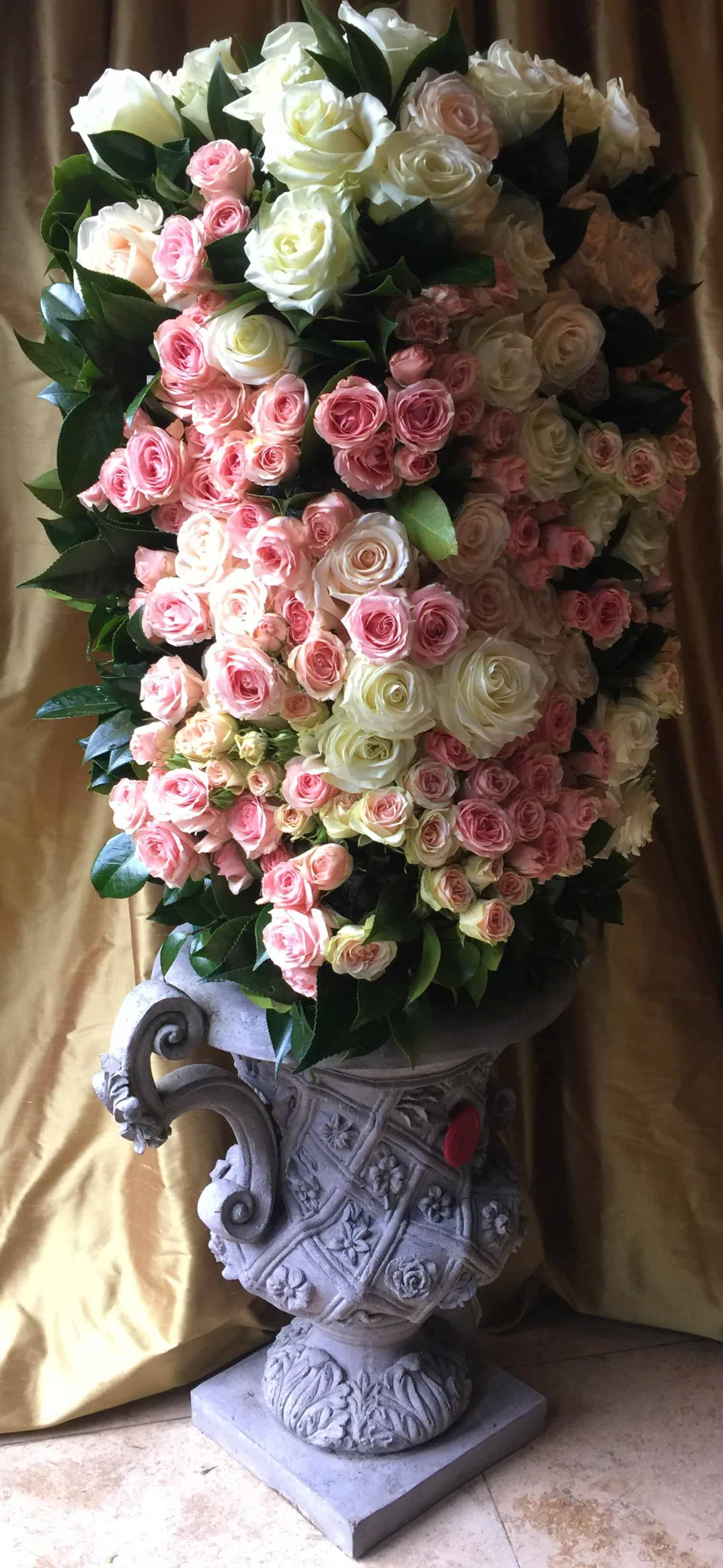Floral urn with ivory roses, blush pink roses, peach roses and foliage in an ornate stone urn