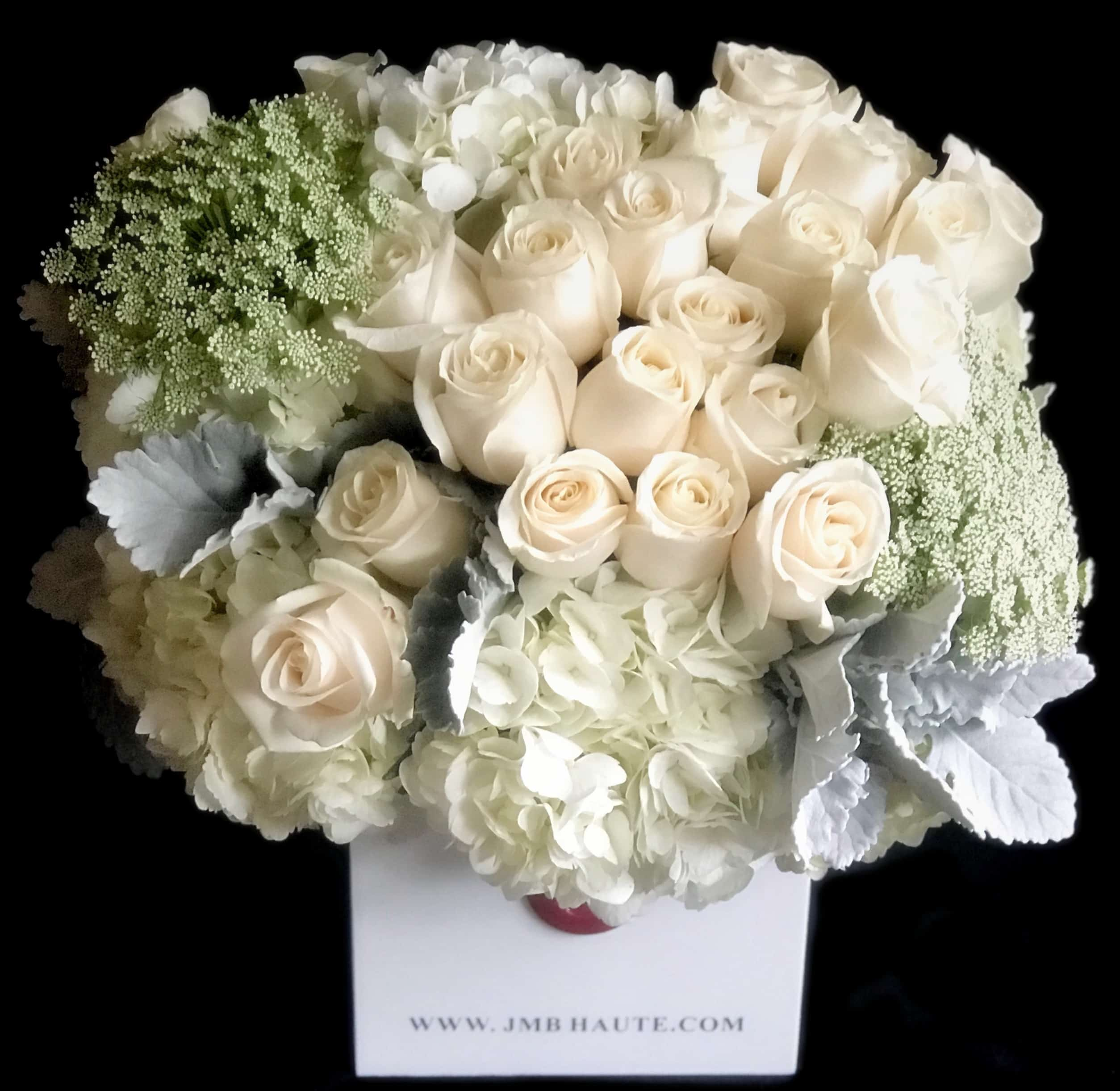 White flowers including, white roses, white hydrangea and seasonal white foliage in our custom acrylic box
