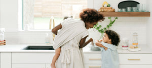 Mother washing clothing stains with daughter