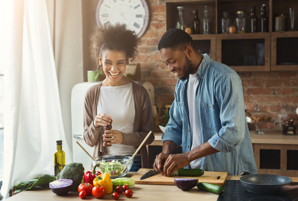 Healthy young couple cooking in the kitchen