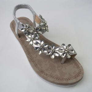 A silver toe-ring sandal with crystal flower embellishments trailing from the toe-ring to upper-strap.