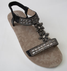 Black crystal sandals with an adjustable back-strap.  Straps with rectangular and floral crystal embellishments. White outsole. Scrunch-textured elastic straps for stretchable comfort and security.