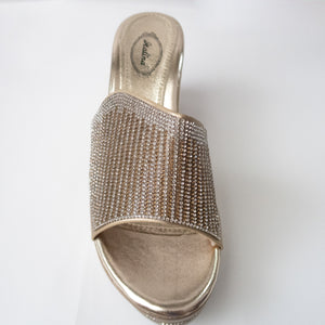 Gold slip-on wedges with crystals embellishing the upper strap. (birds-eye view)
