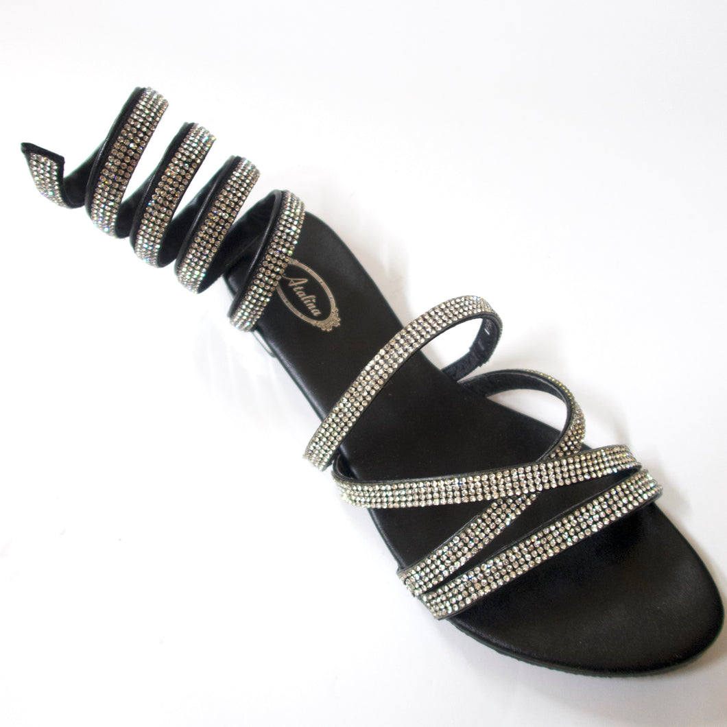 Black flat sandals with a spiral, crystal-embellished wraparound ankle strap. Unique & stylish crystal-embellished wraparound ankle coil. Upper straps embellished with silver crystals. Silver-metallic heel.