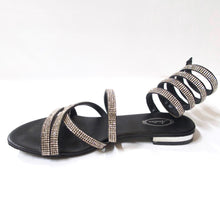 Load image into Gallery viewer, Black flat sandals with a spiral, crystal-embellished wraparound ankle strap. Unique & stylish crystal-embellished wraparound ankle coil. Upper straps embellished with silver crystals. Silver-metallic heel.