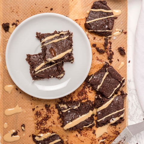 brownie pieces drizzled with peanut butter on a plate on a wooden board