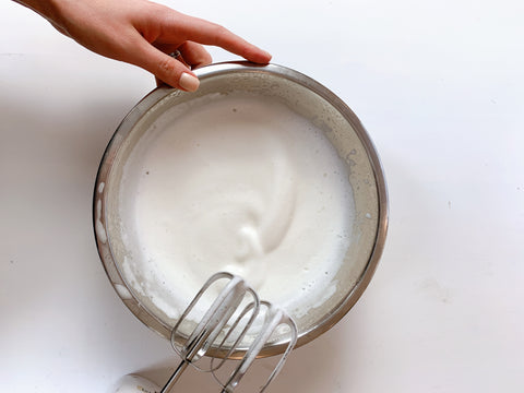 whipped aquafaba and hand and whisk