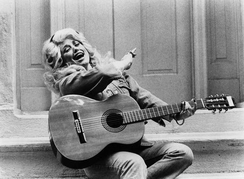 Black and white photo of Dolly Parton laughing and playing the guitar