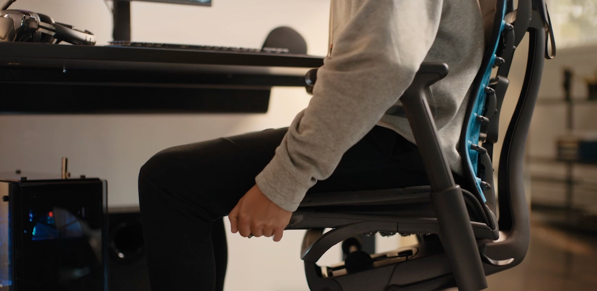 A close-up video of the side of a black Embody Gaming Chair adjustable seat depth mechanism being adjusted by a person in a sweatshirt and pants.