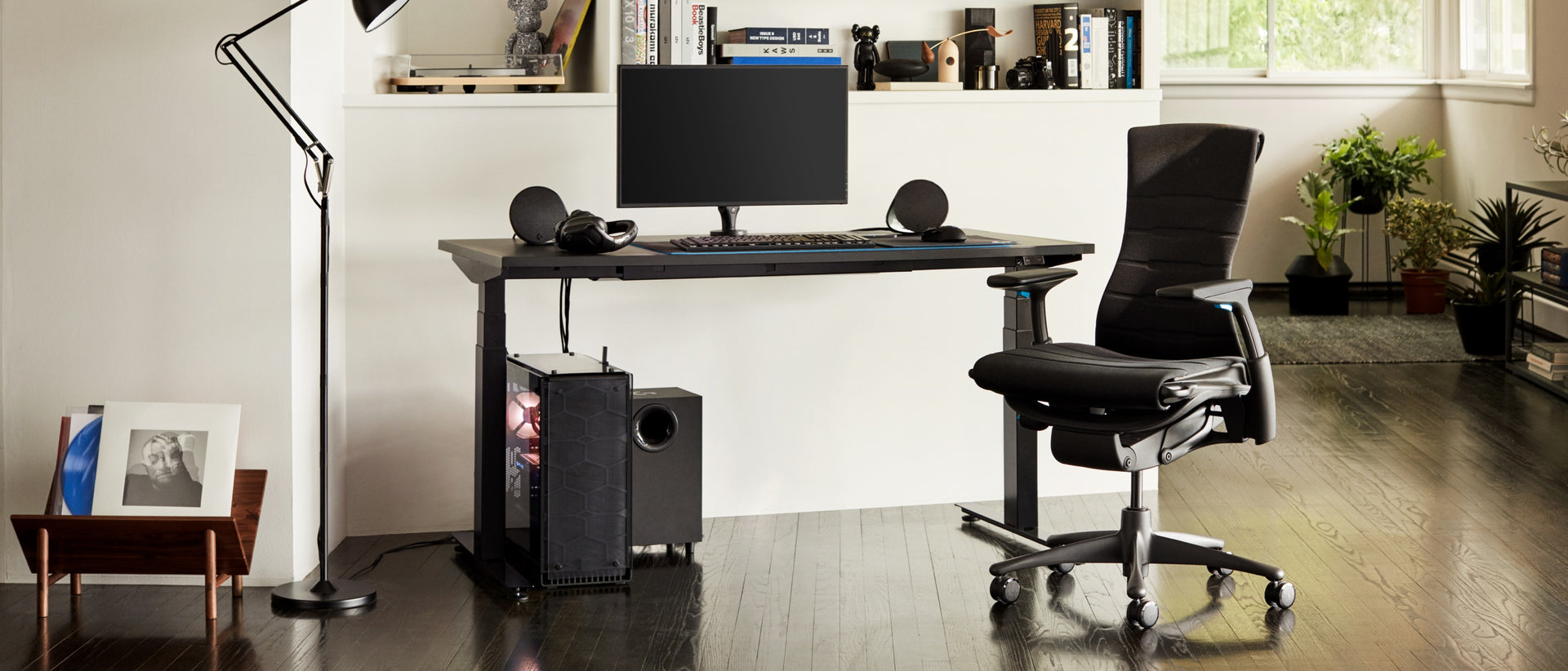 A residential setting features the full setup, including the Embody Gaming Chair, Ollin Monitor Arm, and Nevi Gaming Desk, in the daytime.