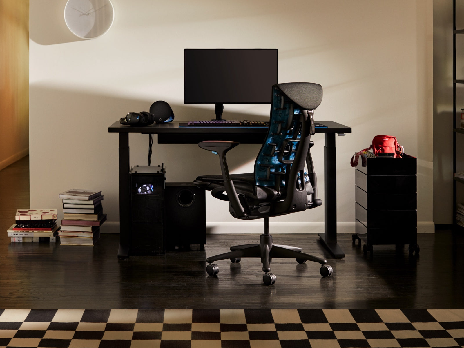 The full set-up from Herman Miller and Logitech G together, including the Embody Gaming Chair, the Nevi Gaming Desk and Ollin Monitor Arm, with additional gaming accessories – all in front of a built-in bookshelf in a residential setting.