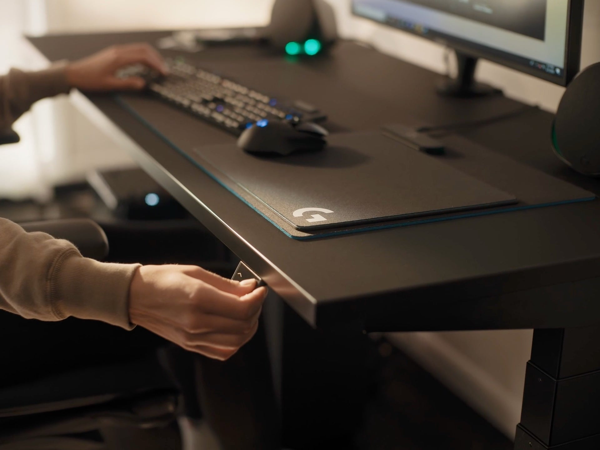 A video features a hand pressing on the lit-up switch on the Nevi Gaming Desk, which raises or lowers its height.