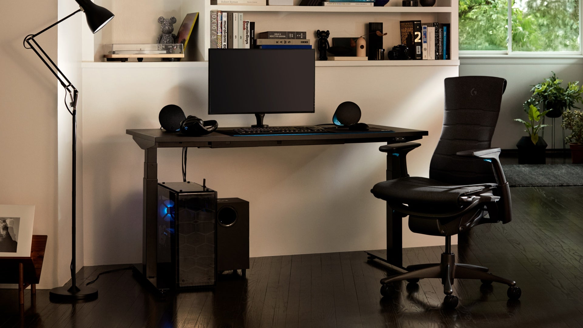 A residential setting features the full setup, including the Embody Gaming Chair, Ollin Monitor Arm, and Nevi Gaming Desk.