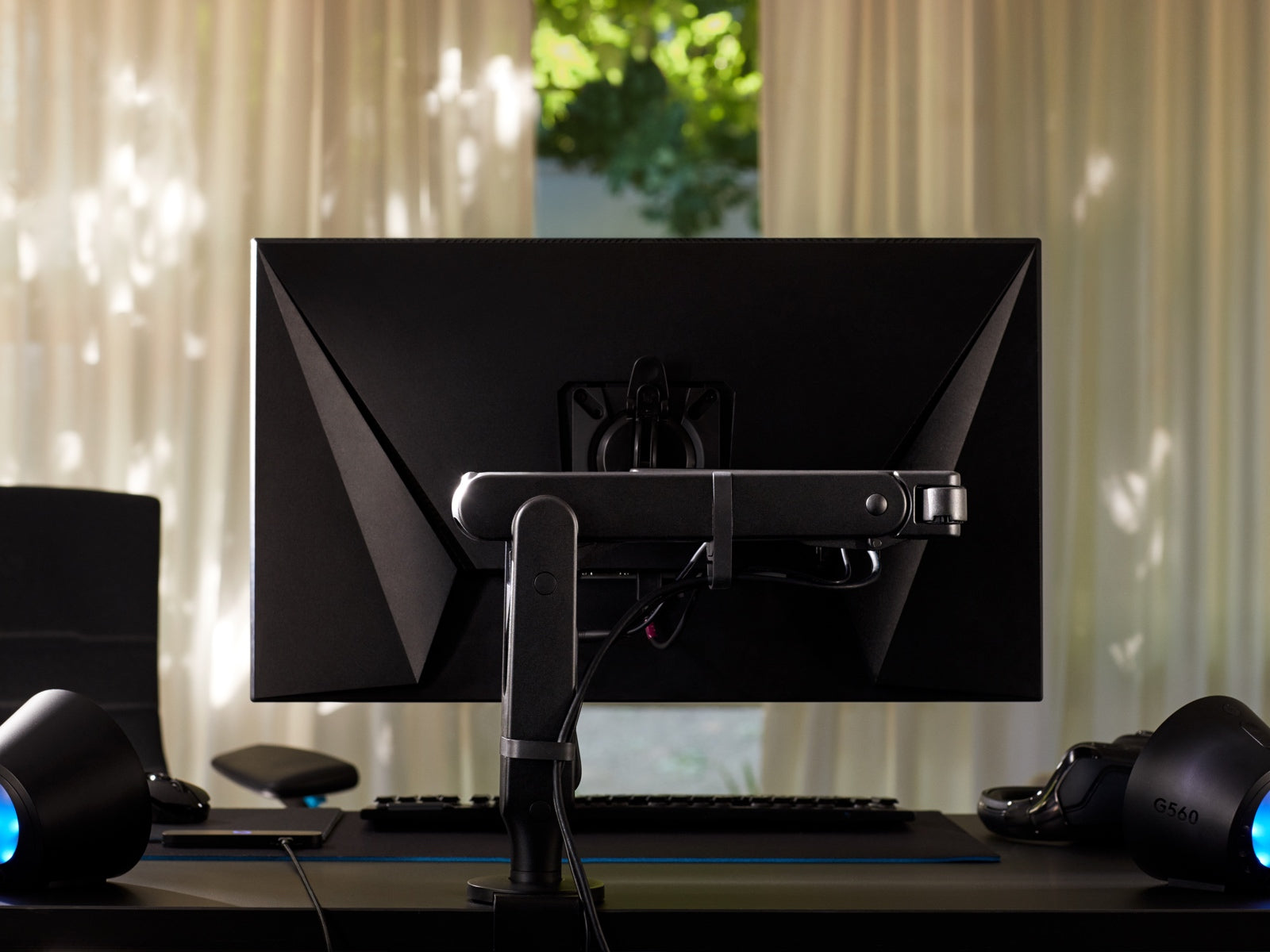 The back of a monitor attached to the Ollin Monitor Arm highlights the cable management system.