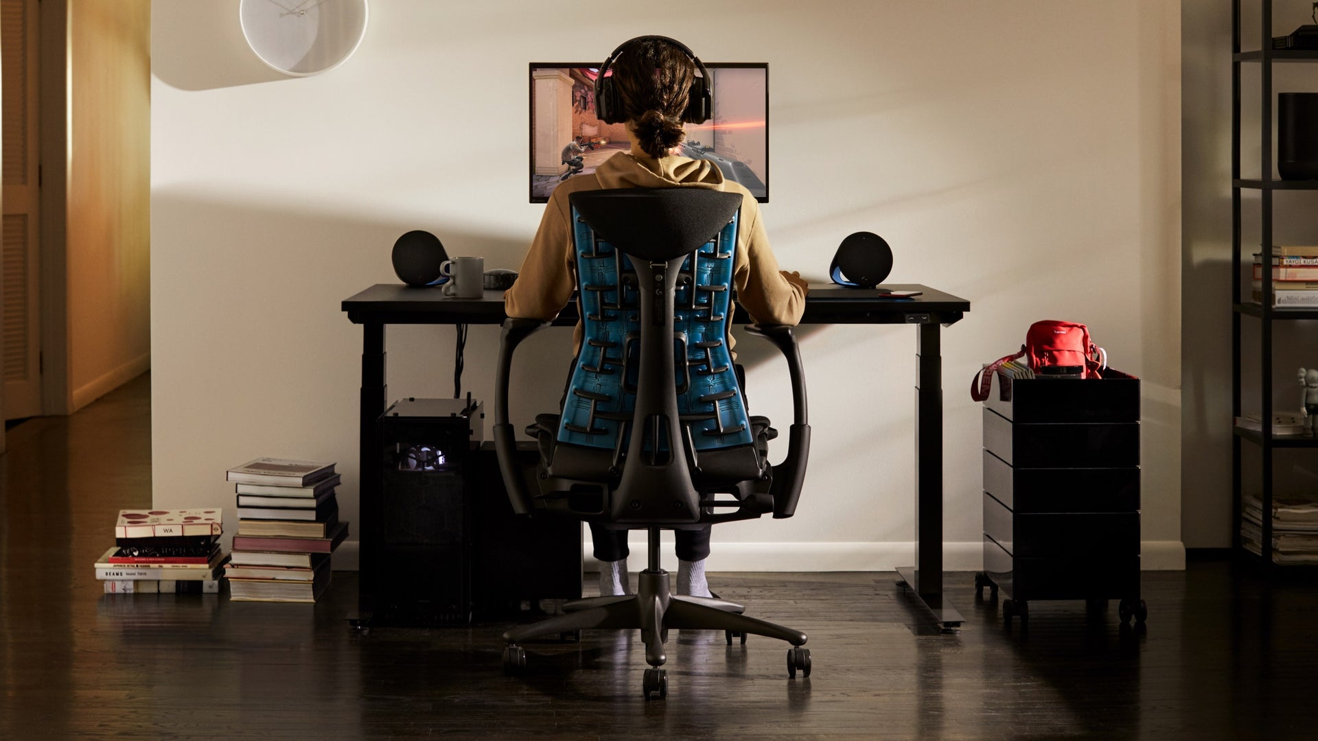 A person sits in the Embody Gaming Chair and looks at a monitor attached to the Ollin Monitor Arm, which sits on top of the gaming desk in a residential setting.