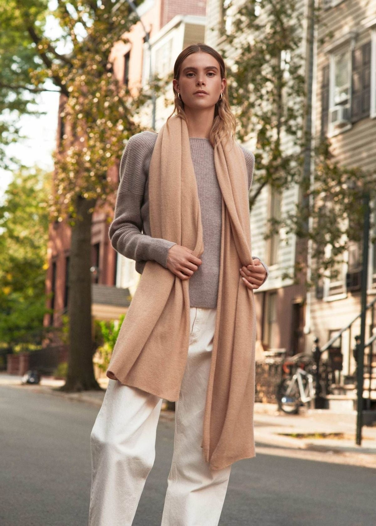 woman wearing the camel color cashmere travel wrap by white + warren