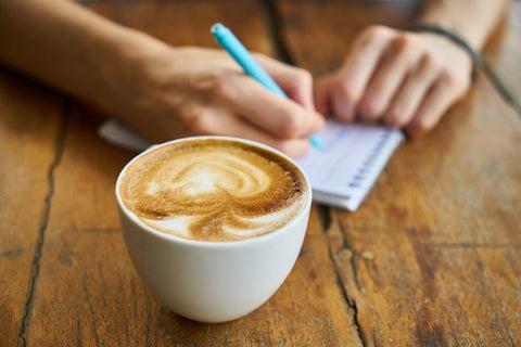 man writing with a cup of coffee on the table