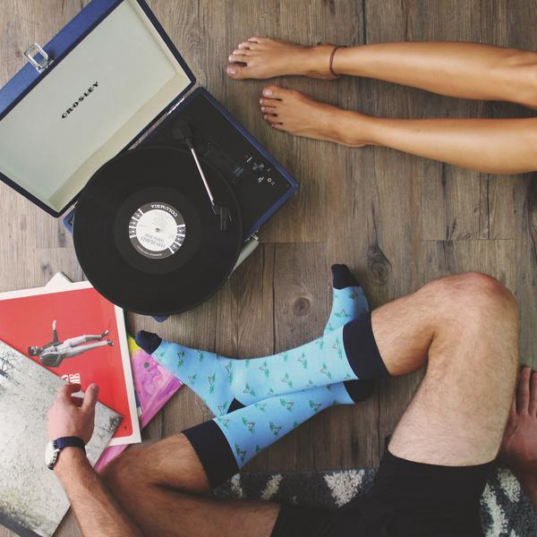 man and women sitting with record player and blue patterned socks
